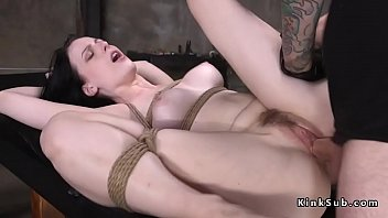 Pale gagged dark haired slave Alex Harper tied up on a black table with legs in the air gets ass plugged with sex toy