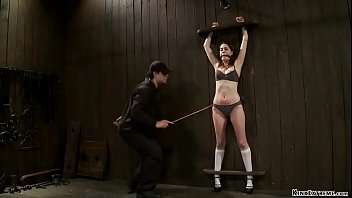 Gagged brunette slut in lingerie Lori Adorable is shackled in wooden stocks to the wooden wall gets caned by master Orlando then made ride Sybian on device bondage