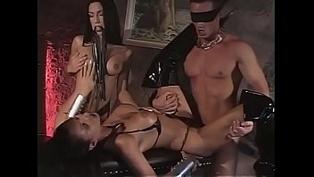 A hot slave in latex dress and mask has a cock in the ass and a dildo in the pussy