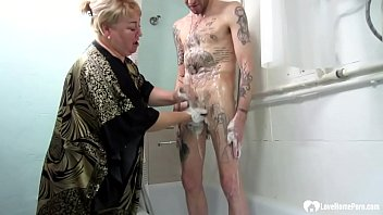 Stepson gets a nice cock pleasuring surprise from his stepmom while taking a shower.