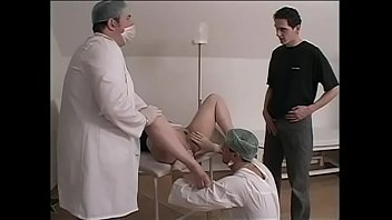 Darkhaired girl in ponytails kneels was invired by surgical doctor to take part in bisexual action