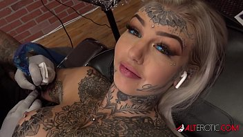 Beautiful busty blonde uses a toy while having her arm tattooed