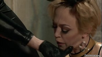 Gimp Bill Bailey shoves big cock down throat of big boobs blonde MILF in latex Dee Williams then makes her kneel on rice and fucks her pussy