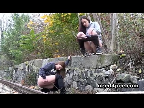 2 girls on park bench peeing